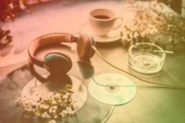 Table with headphone, LP, CD, coffee and cigarette and white flowers